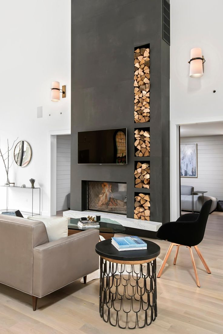 This modern living room turns its firewood storage into an eye-catching part of the decor! The dark gray of the wall helps the color and texture of the stacked wood pop.