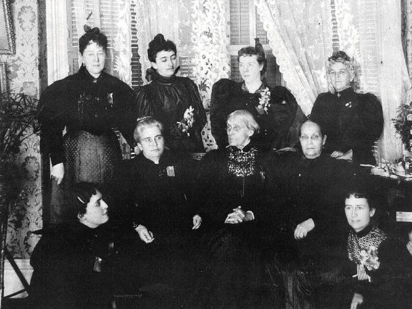 1896 meeting of Suffragist leaders: standing (l to r) Ida Husted Harper, Selena Solomons, Carrie Chapman Catt, Anne Bidwell, (seated) Lucy Anthony, Dr. Anna H. Shaw, Susan B. Anthony, Ellen Clark Sargent, and Mary Hay.