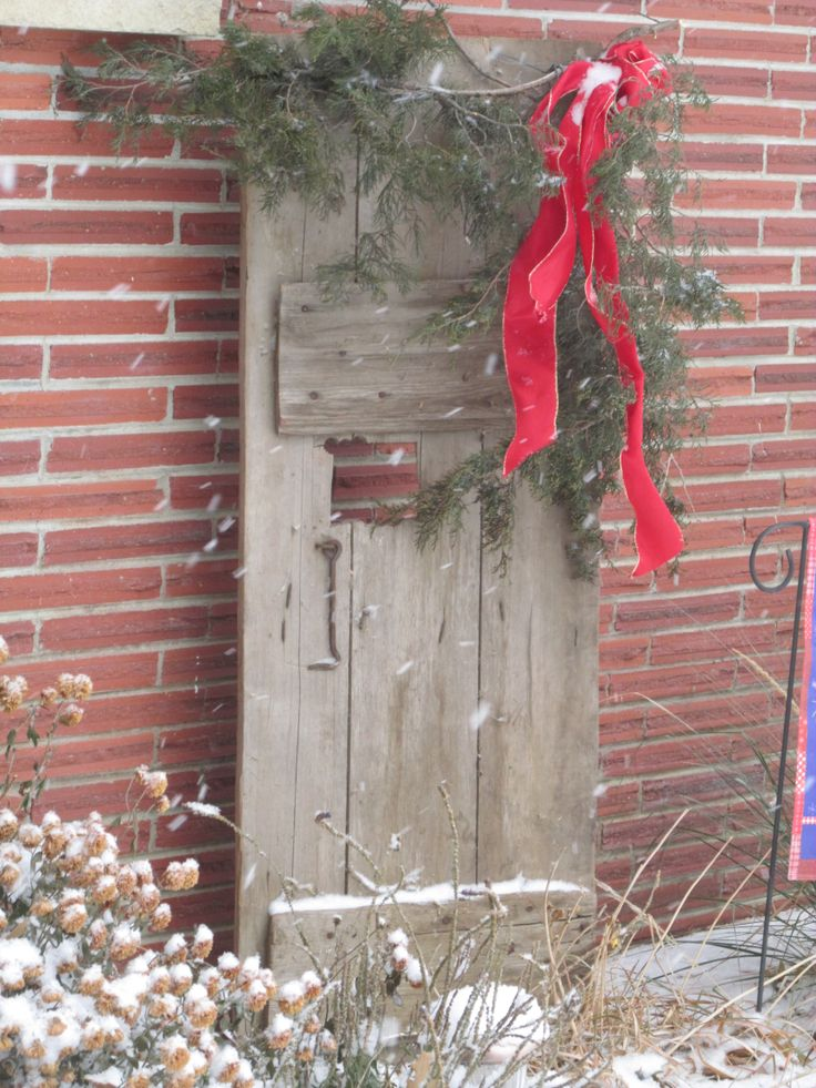 Use an old barn door, add cedar branches & ribbon...Merry Christmas!