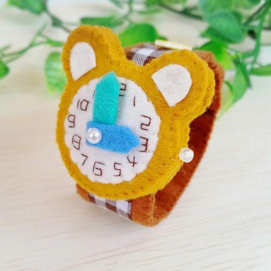 フェルトで作ったおもちゃの腕時計です。時計部分は可愛いクマ型で、文字盤の数字は全てひとつひとつ手刺繍しています。長針と短針はお好きな位置へ動かす事ができます。ベルトの着脱はボタンで、三段階の長さ調節が可能です。お子様のごっこ遊びや普段のお洒落、ディスプレイなどに。またプレゼントにもおすすめです。●カラー:時計部分…黄土色   ベルト…茶色のギンガムチェック柄●サイズ:ベルト長さ 18cm●素材:フェルト、ビーズ、ファブリックテープ、ボンド●注意事項※小さなパーツや一部にボンドを使用していますので、お子様が口に入れたりしないよう充分にご注意ください。※時計の針は同じ方向に回し過ぎると、縫い止めている糸が切れたり、フェルトが傷んで破損の原因となりますので、同じ方向に一周以上回さないようにお願い致します。※出来るだけ丈夫に作ってはいますが、フェルトの性質上、またハンドメイド品のため市販品のような強度はありません。優しくお取り扱い頂けますようお願い致します。●制作者: gokko…