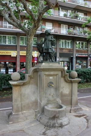 This picture is of a statue titled Little Red Cap Fountain, on Passeig de Sant Joan. This is a sculpture of little girl in a hood with a basket and a wolf, based on the fairytale Little Red Riding Hood. The statue is located near a park, which helps integrate this old legend into daily culture.