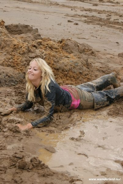 Blonde in muddy waders and leather jacket in the mud