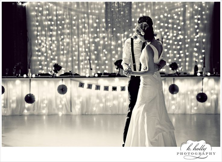 First dance photo with no people in bg. Lights hanging with curtains