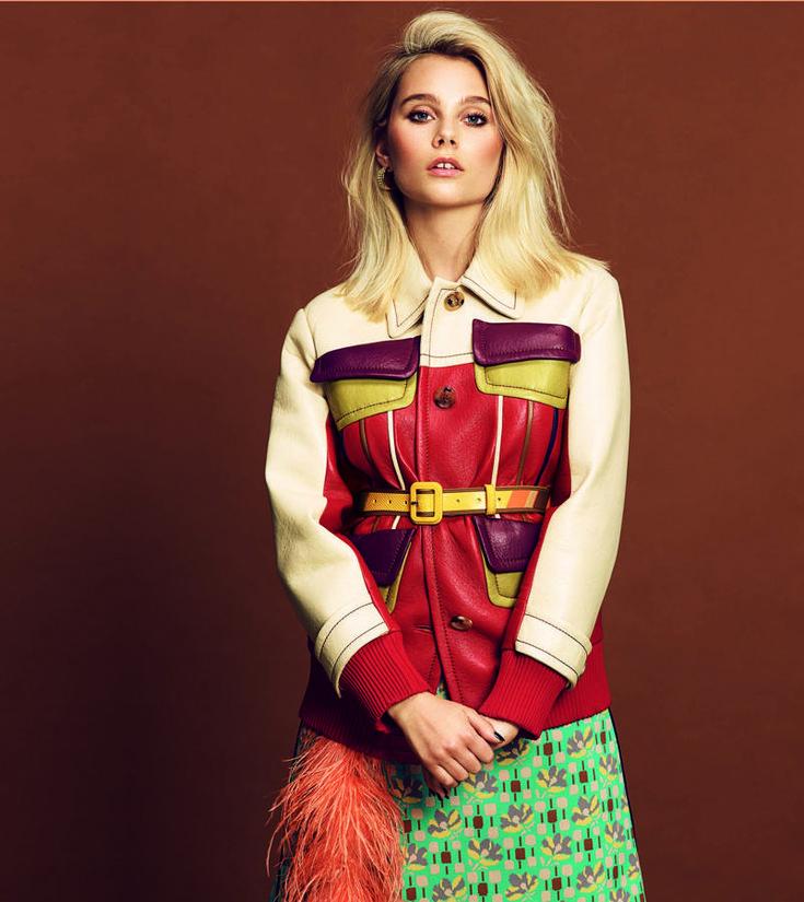 Cazadora de piel multicolor, cinturón y falda con remate de plumas, todo de Prada. Pendientes de aro de Loewe.