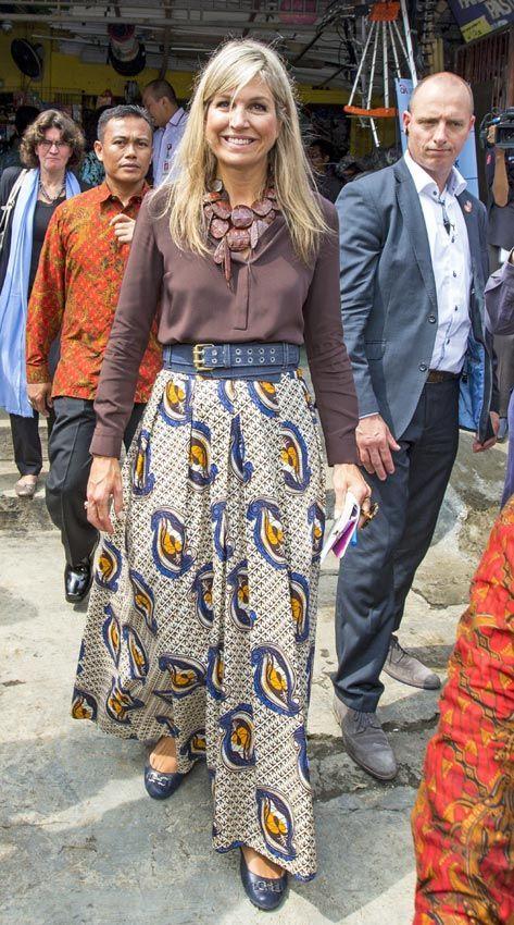 Reina Máxima de Holanda Acto: Visita al proyecto 'Finance Inclusive' en Bogor (Indonesia). Fecha: 31 de agosto de 2016. 'Look': Máxima de Holanda lució una 'maxifalda' con estampado 'étnico', de Millecollines, que combinó con una blusa marrón y un cinturón 'demin'. Como complementos, optó por unas bailarinas con hebilla en azul marino y un collar con piedras en marrón.