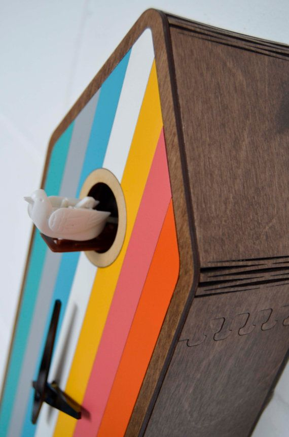 Color House is a modern cuckoo clock inspired by the original Black Forest cuckoo clocks. It has a walnut stained frame complemented by 7 different colors on its face: turquoise blue, grey, sky blue, white, yellow, pink and orange. The large pendulum which is as wide as the clock itself