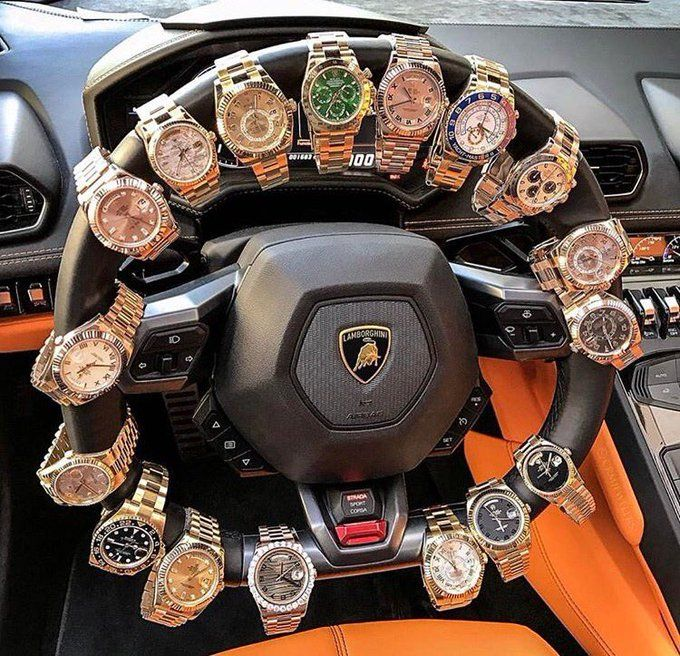 Collection of watches on steering wheel: To remember what time it is or to show  wealth or a way to promote selling watches. Which is it: forgetting time, showing off, or selling watches, etc.
