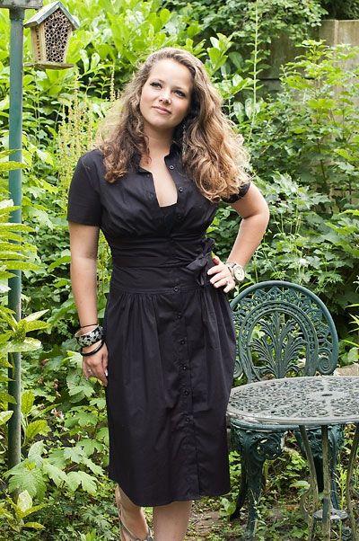 Elegante zwarte knoopjurk met strik-riem van textiel en brede taille.