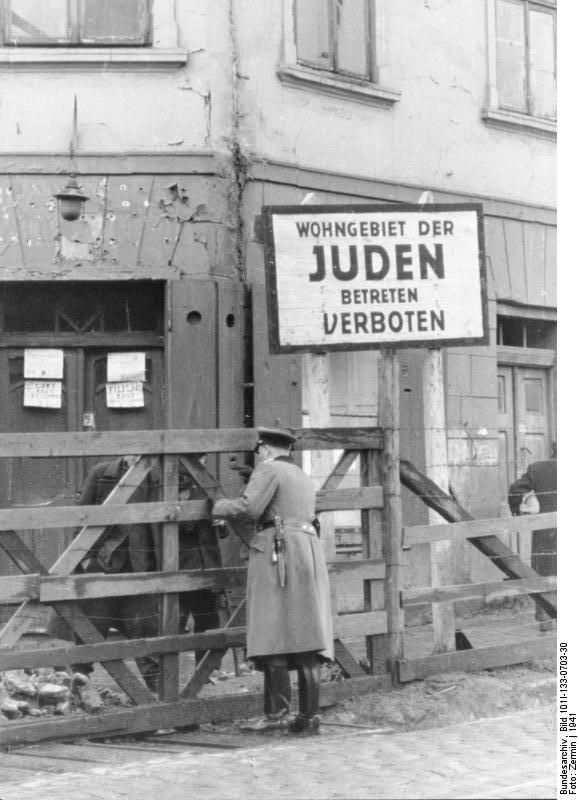 """1941 Zugang ins Ghetto mit Warntafel – """"Wohngebiet der Juden betreten verboten"""" (Quelle: Bundesarchiv Berlin). Entrance to the Ghetto of Lodz. The sign says: """"Living quarters of Jews. Entrance prohibited""""."""