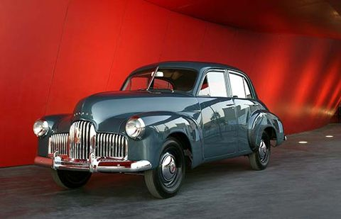 By Land -- Holden Prototype Car No 1, made in 1946. Four door, blue-gunmetal grey sedan with chrome-plated radiator grille, bumper bars, and hub caps. This particular car is the only survivor of three test sedans which became the definitive model for millions of Holden cars, and is now on show in the National Museum, Australia.