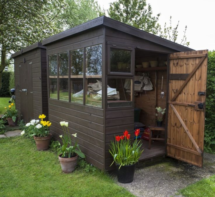 Brown painted garden shed exterior during spring, with open door for storage of tools, flowers, and plant pots