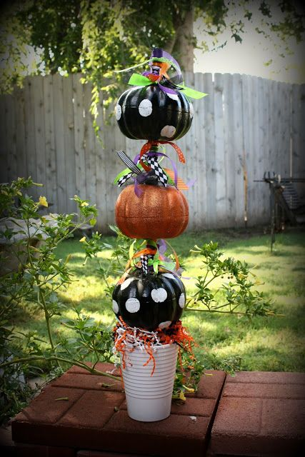 Dollar store pumpkins turned into topiary with wooden dowel, paint and ?? to anchor to keep from turning over