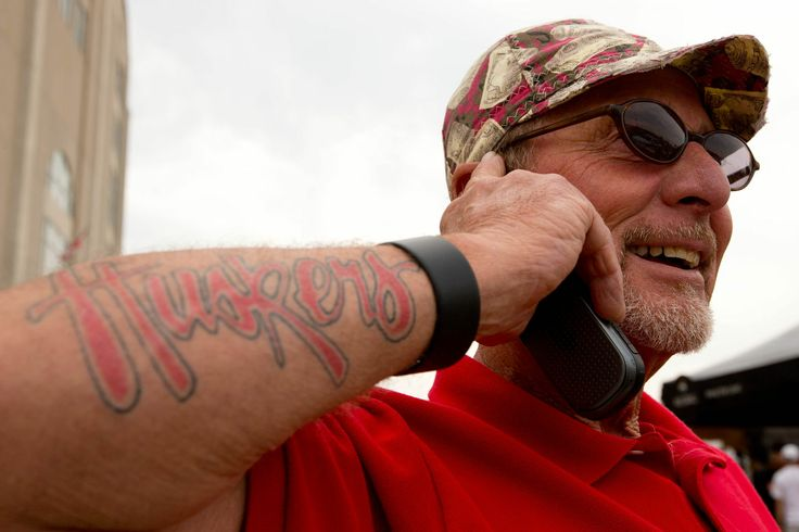 Phil McDonald of Trenton, Neb. talks on the phone with his new tattoo before the annual Husker spring game at Memorial Stadium on Saturday, April 12, 2014. By: SARAH HOFFMAN/OMAHA WORLD-HERALD