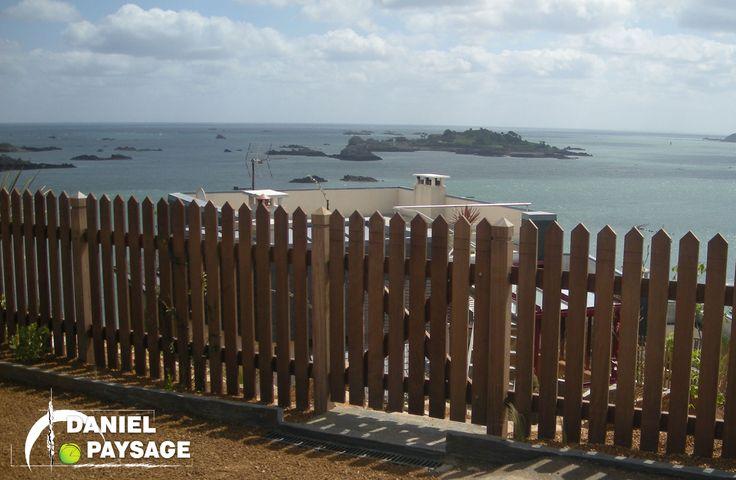 La mise en place de cette palissade en bois exotique donne l'impression de soutenir le paysage.