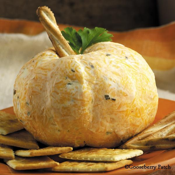 Gooseberry Patch Recipes: Pumpkin Patch Cheese Ball from 101 Autumn Recipes - 16-oz. pkg. shredded extra-sharp Cheddar cheese; 8-oz. pkg. cream cheese, softened; 8-oz. container chive & onion cream cheese; 2 t. paprika; 1/2 t. cayenne pepper; honey-wheat twist pretzel; flat-leaf parsley leaves; assorted crackers