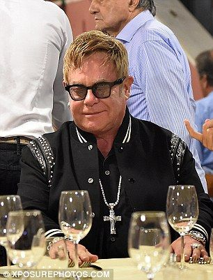 In good spirits: Elton looked content as he chatted to his friends...
