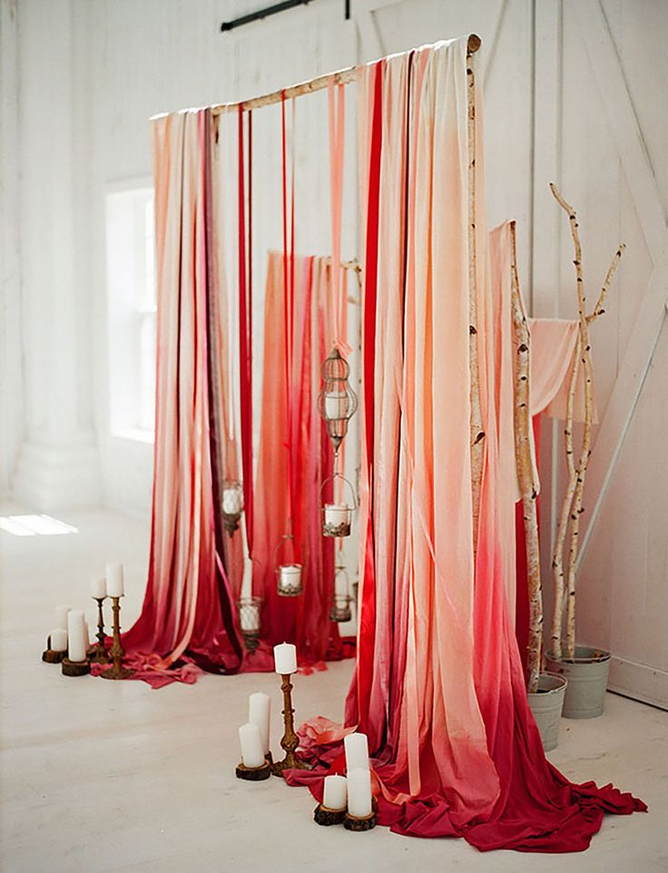 A romantic backdrop of ombré red + pink fabric gave the white-washed barn adramatic punch of style + color. Have you ever seen a prettier use of fabric?! We love how the colors gradually melt into each other and the way the fabric drapesfrom the birch branches.Can you imagine it in different hues?!