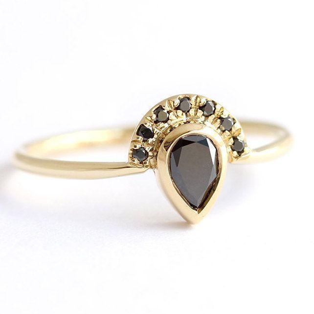 Anillo de compromiso de diamante negro de pera con siete pave diamantes corona en un oro sólido de 18 k. Diseño fino y delicado en un glamoroso de moda antigua.  Banda del anillo: 1,3 mm Materiales: 18k oro sólido, pera de 0,25 quilates corte diamante negro, siete diamantes negros de 1 mm. El anillo viene con un certificado de autenticidad.  Otorga una hermosa boda con nuestro anillo de diamante V: https://www.etsy.com/il-en/listing/207815662  Disponible en amarillo, ...