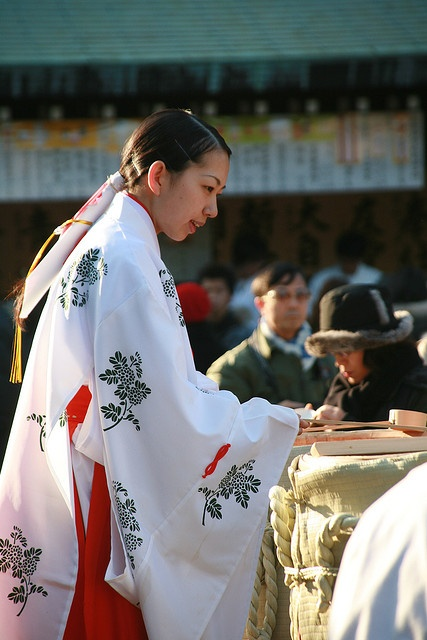 Miko handing out sake at matsuri