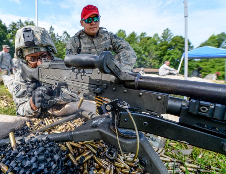 U.S. Air Force Senior Airman Quataisia Marigny, a member of the 116th Security Forces Squadron (SFS), Georgia Air National Guard, fires an M240 machine gun under the watchful eye of Staff Sgt. Alan Glaze, a combat arms instructor from the 116th SFS, during a training exercise at the Catoosa Training Site, Tunnel Hill, Ga., June 26, 2014.(U.S. Air National Guard photo by Master Sgt. Roger Parsons/Released)