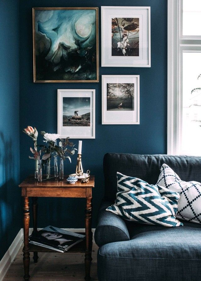 Living room with  dark blue marine walls,  layered art, and a vintage table