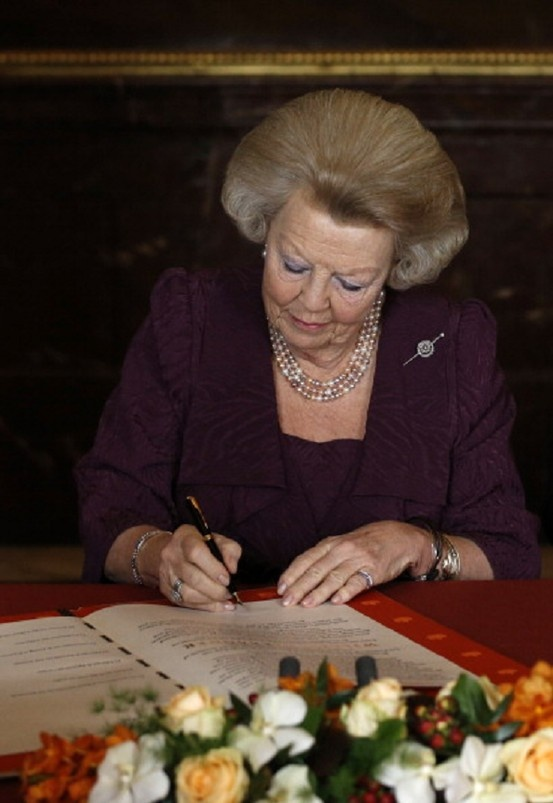 Queen Beatrix of the Netherlands signs the Act of Abdication during a ceremony in the Moseszaal at the Royal Palace on 30 April 2013 in Amsterdam