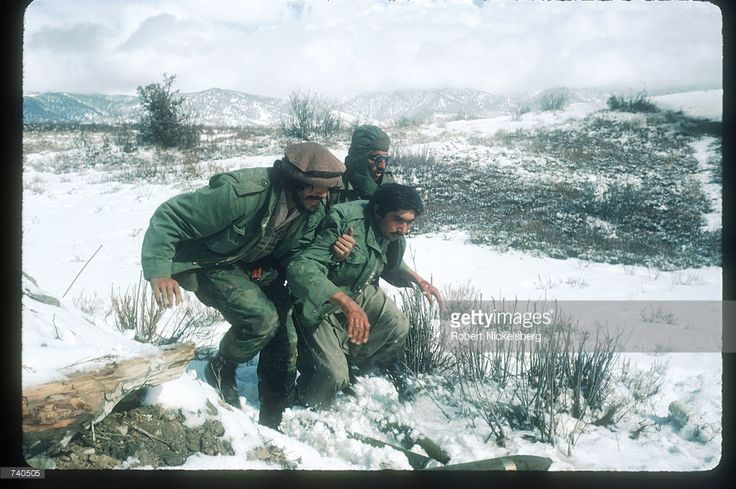 Guerrilla soldiers help a wounded man back to a remote base in the Safed Koh mountains February 10, 1988 in Afghanistan. A Soviet-supported communist coup by the People's Democratic Party of Afghanistan led to the USSR's 1979 invasion of the Islamic nation, resulting in ten years of civil war between the Russian-led Government and the US-backed Afghan rebels.