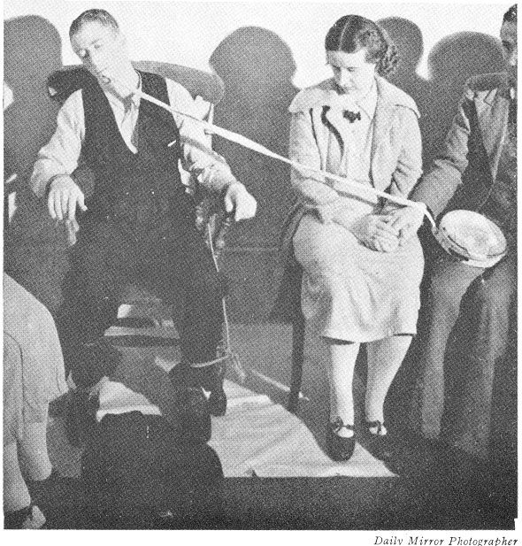 """As often happens, Spirits do work in various way and are often """"playing"""" or testing. This is most probably not the same sitting as on the photograph above to right, as can be seen on the lady's clothing and shoes. This Ectoplasmic Rod lies on the sitters hand but is attached to this tambourine."""