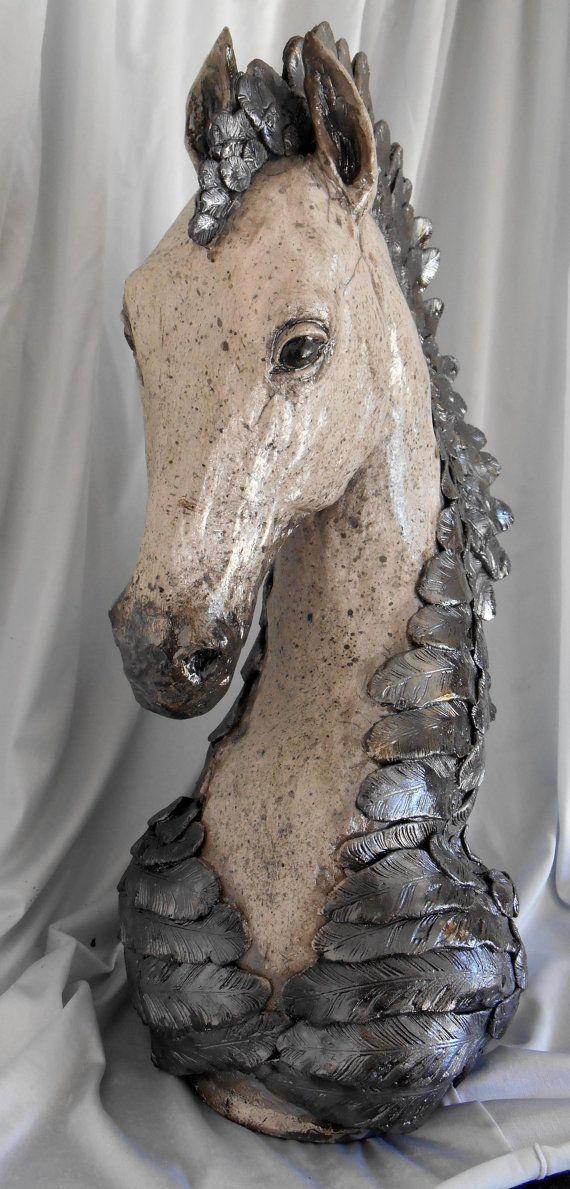 Raku, Ravens Mane paard beeldhouwkunst 15 inch hoog, 10 op het breedste punt van voorkant naar achterkant en 6 breed bij base.  Dit is een raku paard hoofd ik gewoon voor de lol maakte! Hij heeft de veren voor een manen die goed met zijn dapple grijze jas gaat. Dit is een echt uniek kunstwerk. De veren zijn erg zwart met een hoge glans, zijn vacht is een zilver-grijze kleur die goed met zijn manen raven veer gaat. Dit zal is een decoratieve stuk en een grote aanvulling op elke paard lovers…