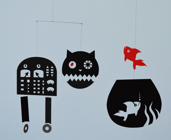 "This mobile consists of a cat, a goldfish in a bowl and a red goldfish. It hangs approximately 14"" wide by 12.5"" tall. It is hand crafted with laser-cut card stock paper (black and red), string, metal beads and metal wire.  All delicious mobiles™ are uniquely designed for people of all ages. With their simple color scheme, they would be a nice addition to any room in your home. And, of course, they would make great gifts to anybody for any occasion.  It is ready to hang and could be adjusted…"
