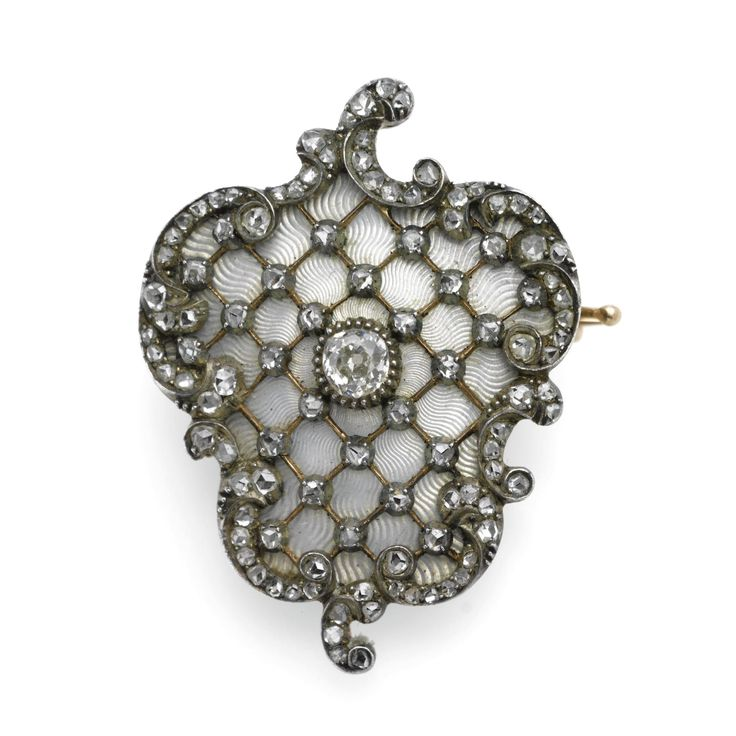 A FABERGÉ GOLD, DIAMOND AND GUILLOCHÉ ENAMEL BROOCH, WORKMASTER: MICHAEL PERCHIN, ST. PETERSBURG, 1899-1903 the surface enamelled in translucent oyster white over wavy sunburst engine-turning radiating from a diamond and applied with diamond-set trellis work within rococo surround, with workmaster's initials and scratched inventory number 70079, 56 standard.