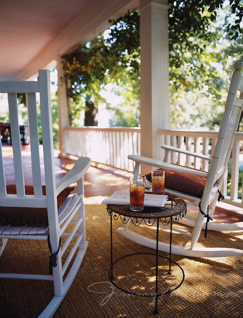 Sun Shines Onto A Rocking Chair Front Porch With Two Empty
