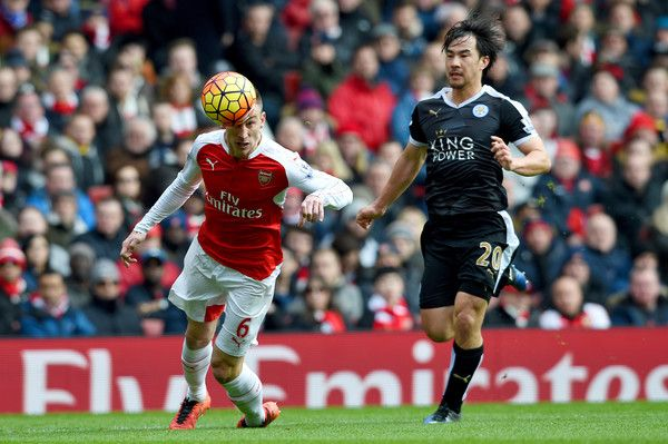 Shinji Okazaki Photos - Laurent Koscielny of Arsenal heads the ball back to Petr Cech under pressure from Shinji Okazaki of Leicester City during the Barclays Premier League match between Arsenal and Leicester City at Emirates Stadium on February 14, 2016 in London, England. - Arsenal v Leicester City - Premier League