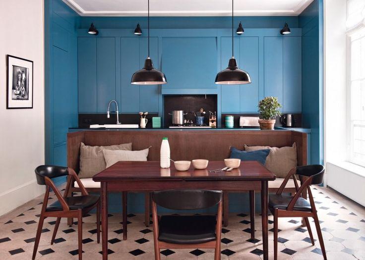 <p>Dans cette pièce à vivre colorée, le coin cuisine est délimité par un bleu vif, contrasté par les couleurs plus sombres de la partie salle à manger....