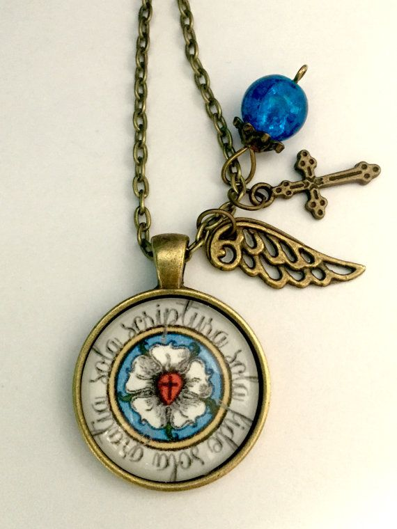 Beautiful handcrafted glass pendant necklace with Martin Luthers Seal surrounded by the Latin inscription Sola fide, sola gratia, sola scriptura which means Faith alone, grace alone, scripture (word) alone. Necklace comes in your choice of three metal finishes: antiqued copper, bronze, or silver; along with a wing and cross charm and a blue bead. Great confirmation gift, and as a subtle proclamation of your Lutheran faith. I create the design and print on high quality paper, then secure to a…
