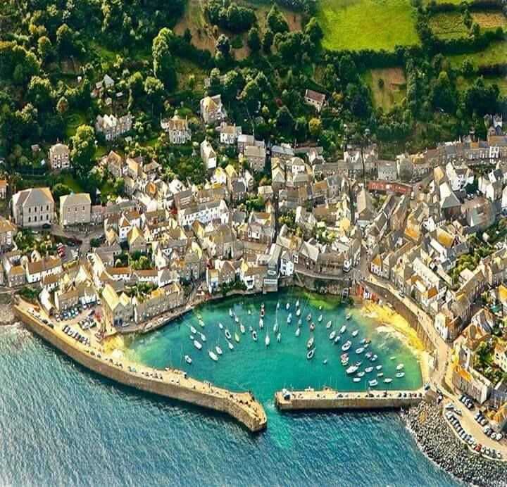 "AERIAL VIEW   Mousehole, Cornwall: 'Mousehole (pronounced ""mowzel"") is named after a small cave of that name. It is famous for its narrow granite streets and tiny harbour, the landing place for the Knights of St John on their return from the Holy Land. Po"