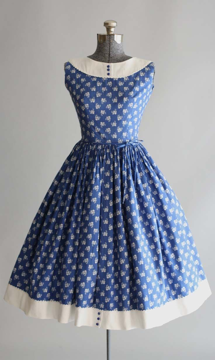 This 1950s Lanz Originals cotton dress features a white flower and heart print atop a blue background. Contrasting white cotton pique trim and ric-rac trim at neckline and hem of skirt. Sleeveless. Full pleated skirt. Buttons going up back of dress. Attached waist tie.