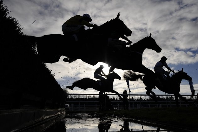 Riders take the water jump in The Burges Salmon Novices' Limited Handicap Steeple Chase at Newbury racecourse on November 29, 2012 in Newbury, England. (Photo by Alan Crowhurst/Getty Images)