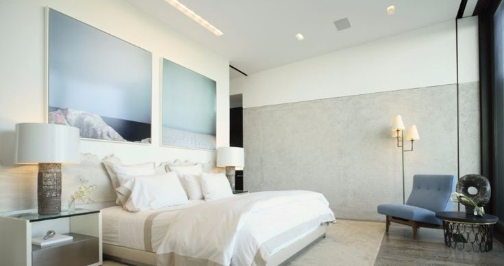 A soothing master bedroom in white and grey with two relaxing photos and tones of white and blue doing the rest of the work.