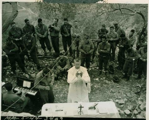 On April 9, 1944 hostilities ceased for one hour on this Italian front line sector during Easter mass services conducted by American soldiers and directed across enemy lines by specifically installed amplifiers (loud speakers) to specifically include German soldiers. Photo: Chaplain Leo J. Crawley says mass to a group of soldiers who were close enough to leave their fox holes to attend. (Italy)