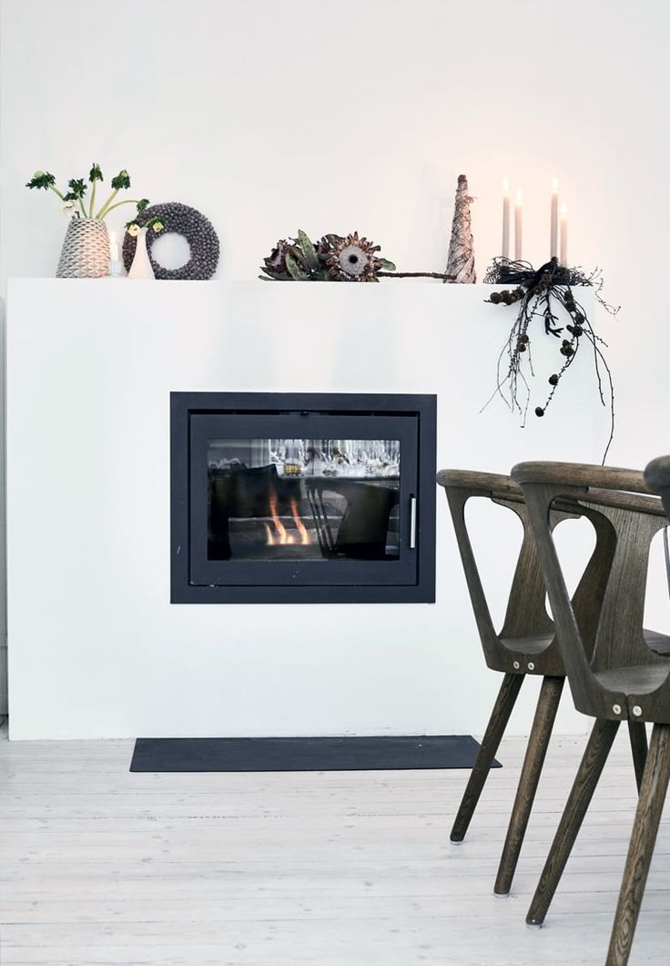 Modern built in fireplace with pine cone wreaths, dried flower stands and a small collection of retro-ceramics on top.