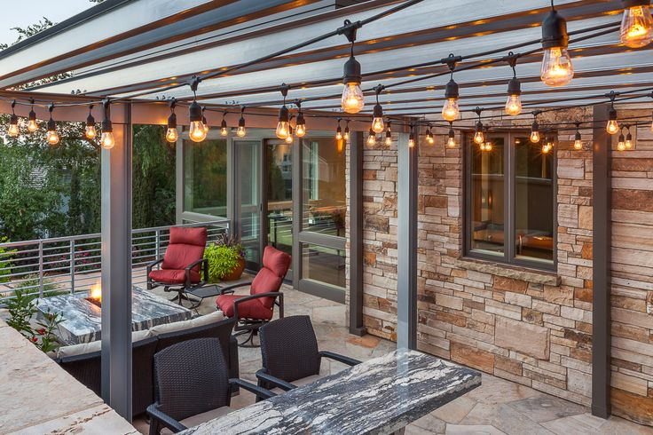 Outdoor patio with industrial style outdoor lighting, light stacked stone  veneer, stone fire pit, stone bar counter, and red patio furniture. - Outdoor Patio With Industrial Style Outdoor Lighting, Light