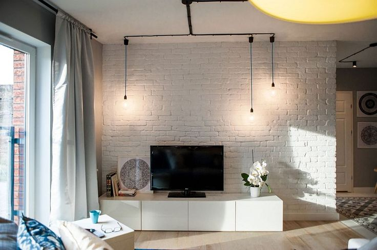 Whitewashed brick wall in the living and minimal industrial lighting - Decoist