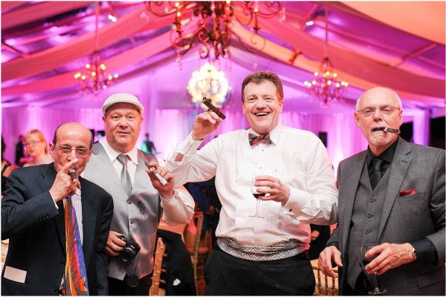Men at cigar bar during wedding | Catering by Susan Gage Catering | Pink and purple uplighting on white tent by Sugar Plum Tents | Elegant and luxury design by DB3 Design | Ana Isabel Martinez Chamorro associate photographer for Mike Buscher Photography