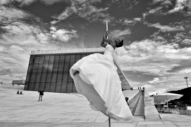 Bride, pole-dancing in her white wedding-dress in front of Oslo Operahouse