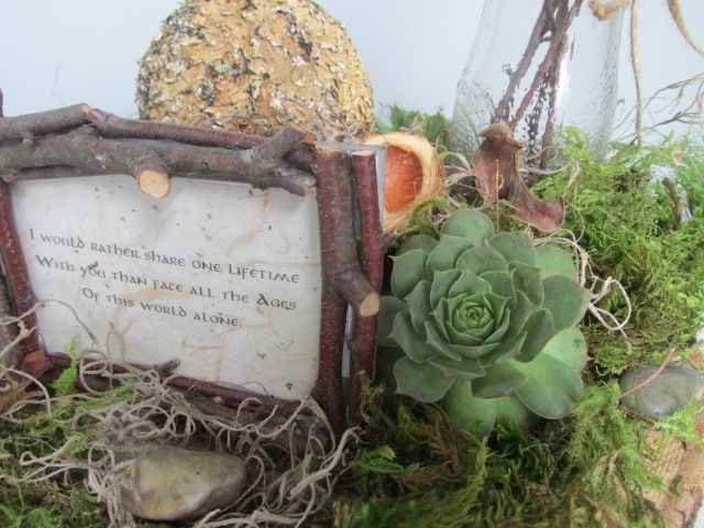 Lord of the Rings/Hobbit inspired centerpiece.  Close up: Green moss, Spanish moss, Hens & Chicks succulents, glass bottle from Hob Lob with twigs, twig frame movie quotes, botanical spheres, a few rocks and some potpourri sprinkles.  All atop wood slices.