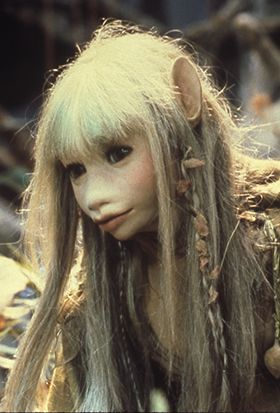 Adolescent female Gelfling. Two-and-a-half feet tall, with long fair hair and gossamer wings. Kira wears clothes with Podling designs.