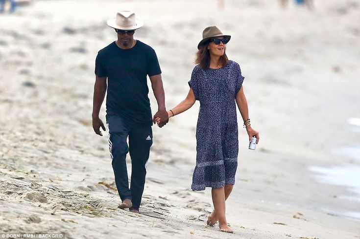 Not hiding it any more: Katie Holmes, 38, and Jamie Foxx, 49, held hands as they strolled along the beach in Malibu on Monday after finally confirming their 'secret' romance