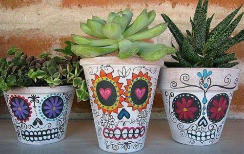 You'll need craft paints, including black and white, brushes and markers, terra cotta pots and plants.