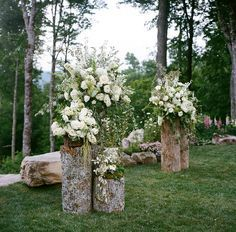 Rustic wedding decor idea with tree stumps to help create the ceremony backdrop